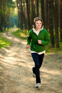 Pretty young girl runner in the forest while listening to music.